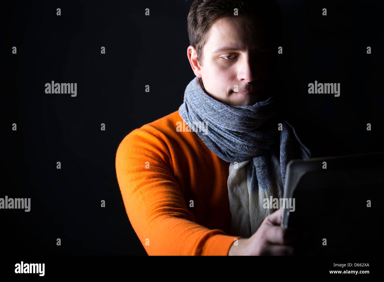 Man on black background watch something on laptop - Stock Image