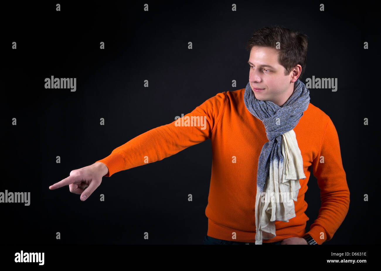 Man on background pointing on something outside frame - Stock Image