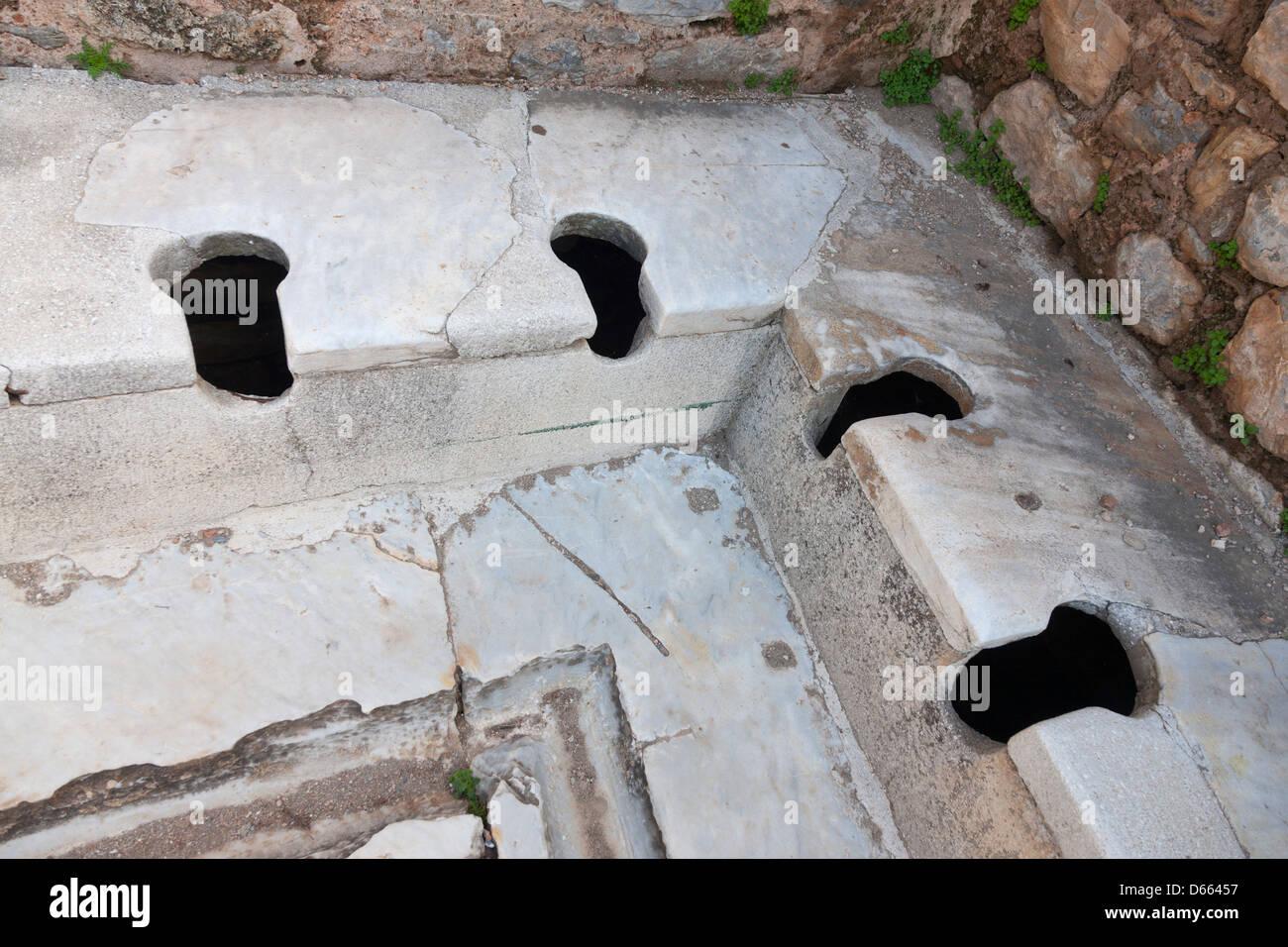 Roman marble toilet seats in the ancient ruined city of Ephesus near Selçuk, Turkey Stock Photo