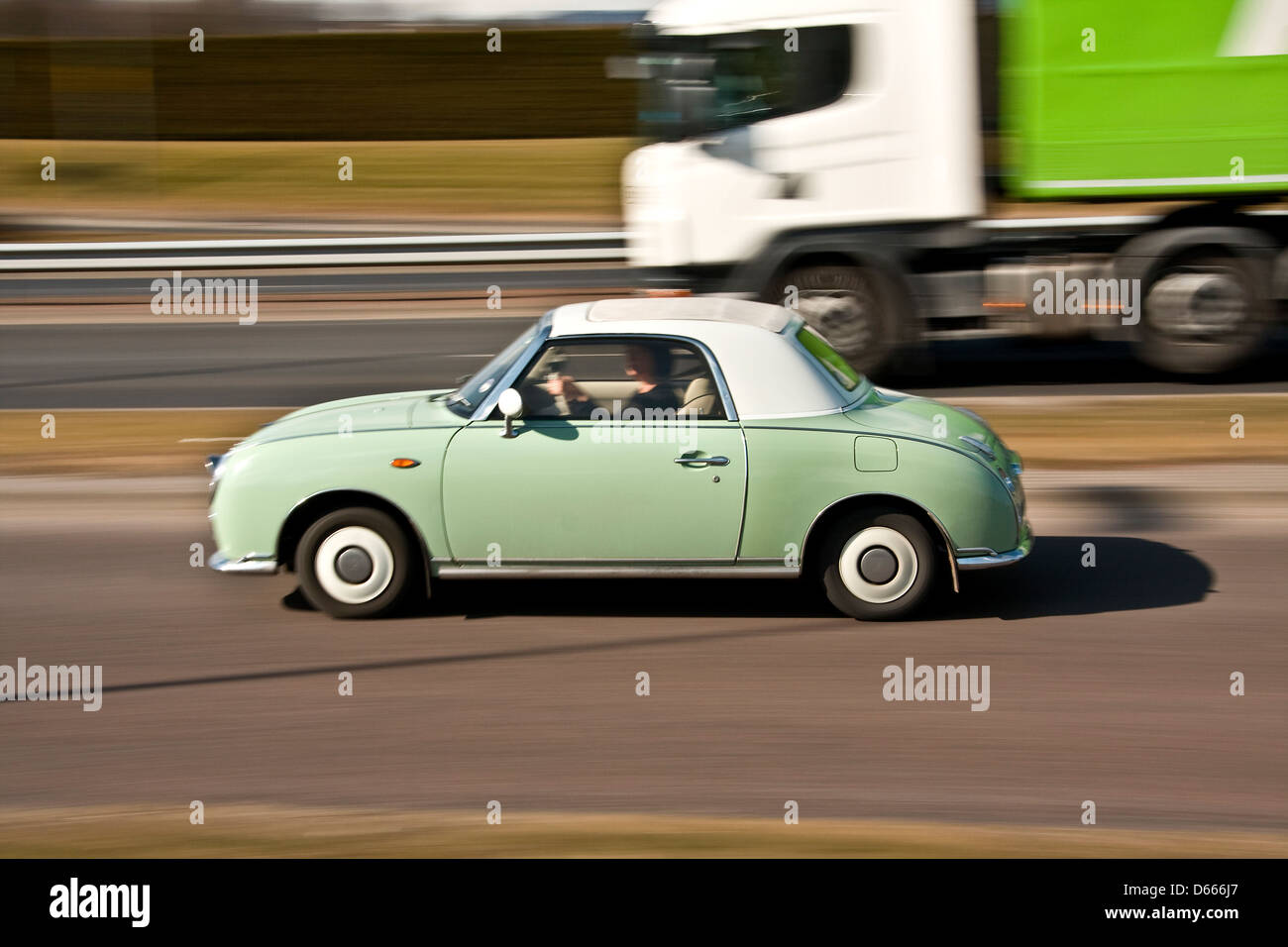 Retro 1960`s style Nissan Figaro Japanese car being overtaken by a ...