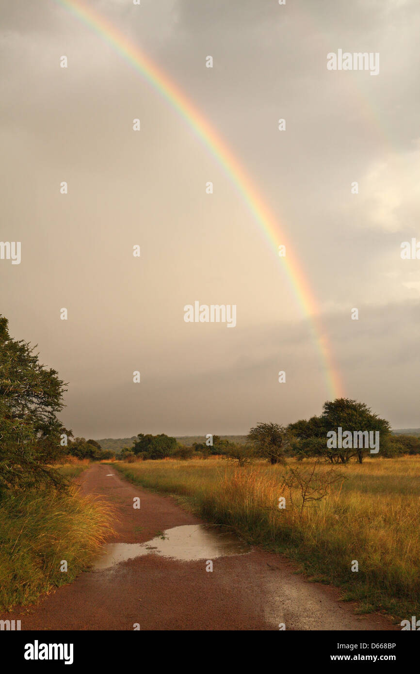 Rainbow over rural road - Stock Image