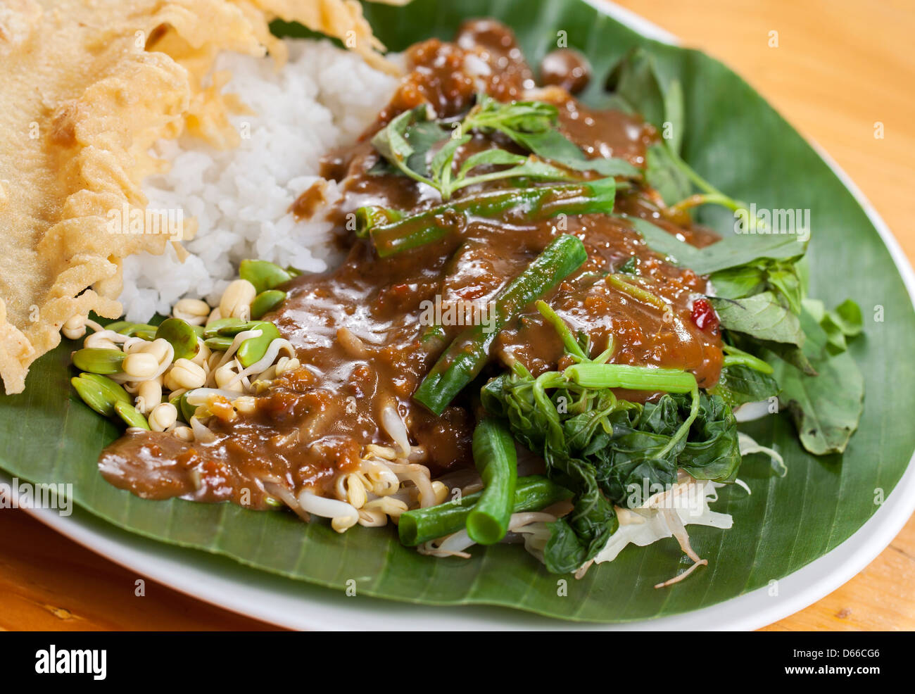 Nasi pecel is a Javanese rice dish served with mix vegetables and peanut sauce - Stock Image