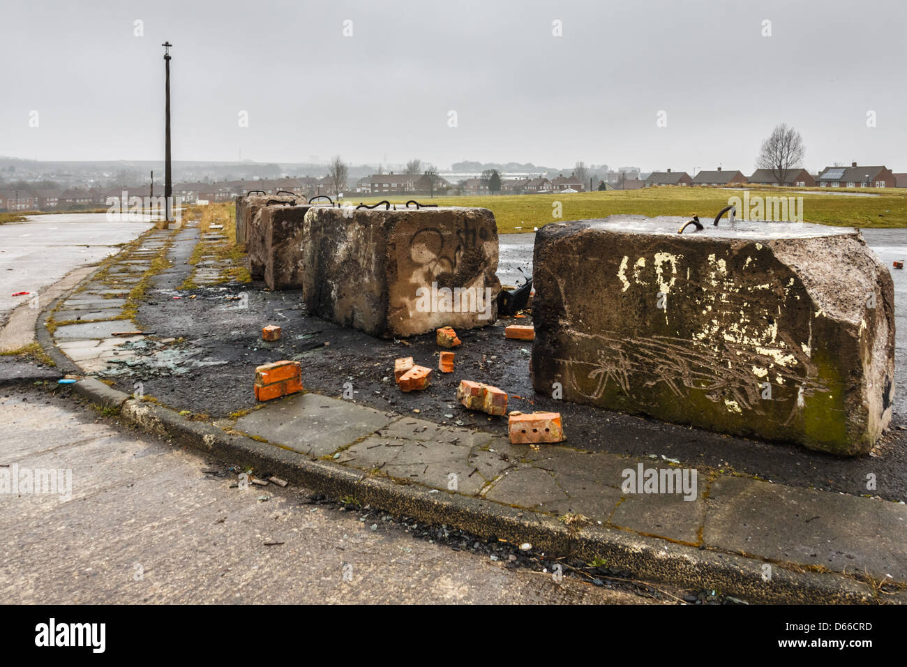 Concrete blocks form a barrier on wasteland created from a demolished housing estate in Pennywell, Sunderland, UK. - Stock Image