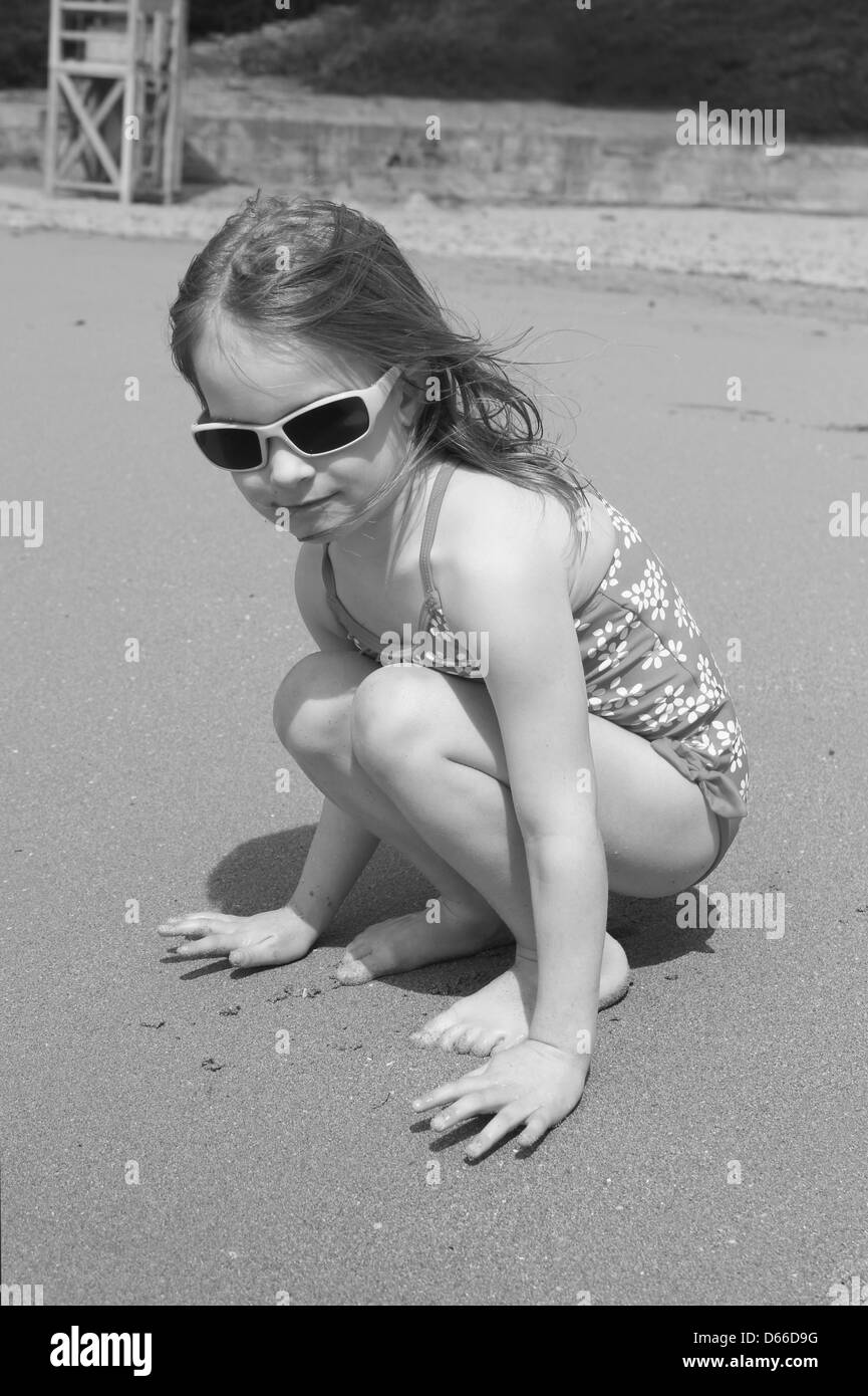 Young girl in swimsuit crouching on the beach - Stock Image