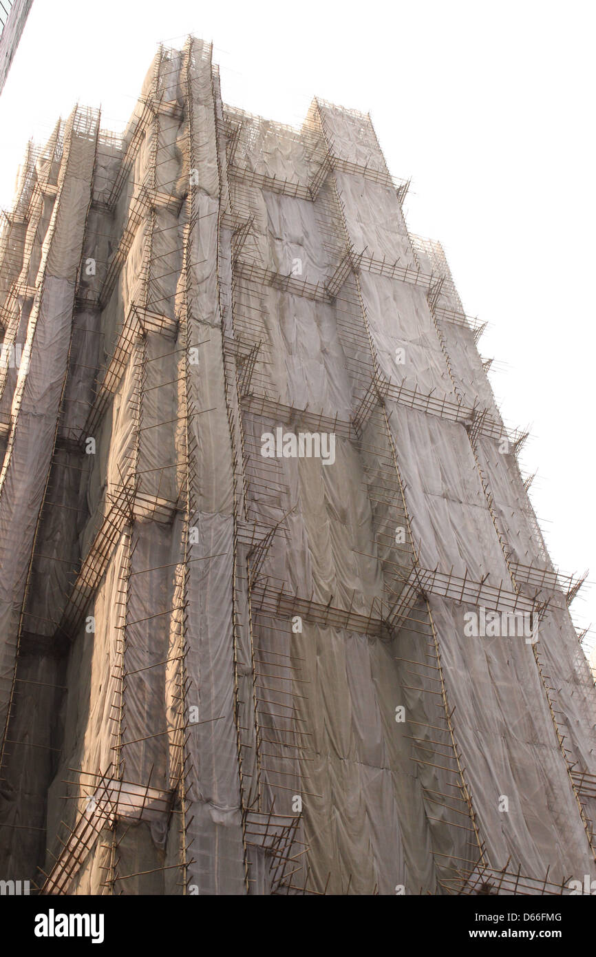 Bamboo scaffolding and netting covers a building undergoing renovation in Hong Kong - Stock Image