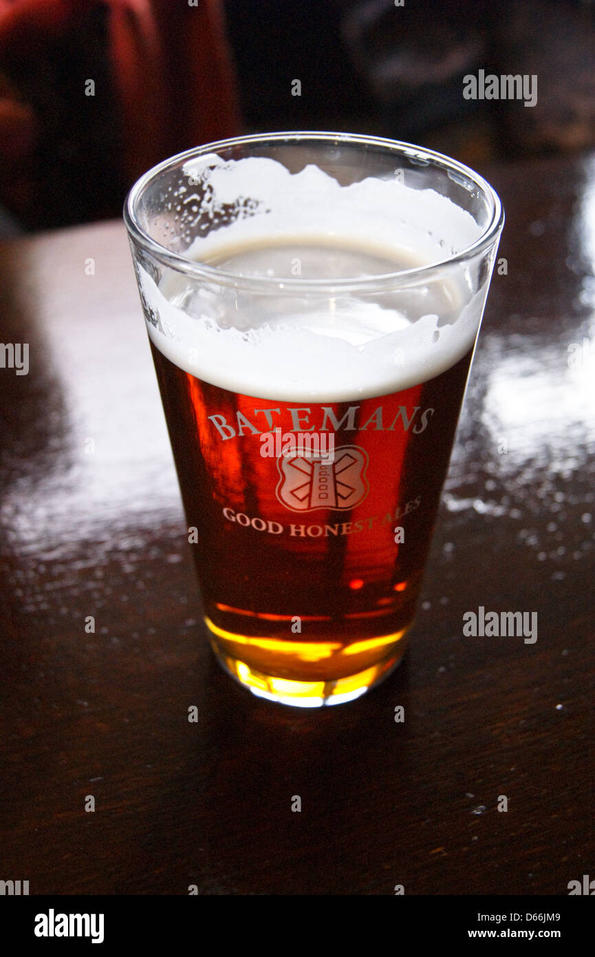 A printed pint glass of Batemans bitter on a bar pub table drinks glasses Stock Photo