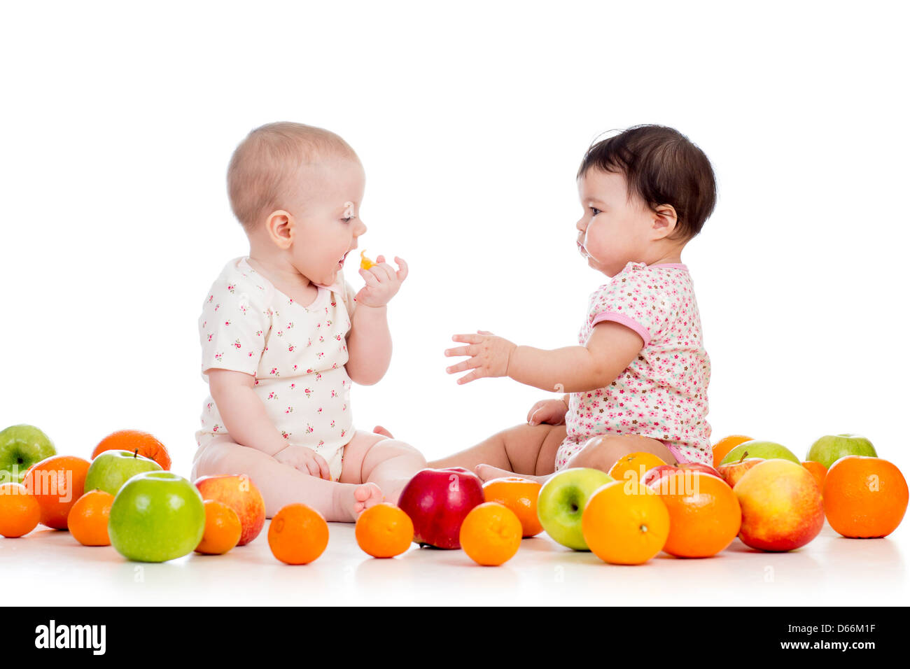 Two children kids eating together healthy food fruits isolated on white background - Stock Image