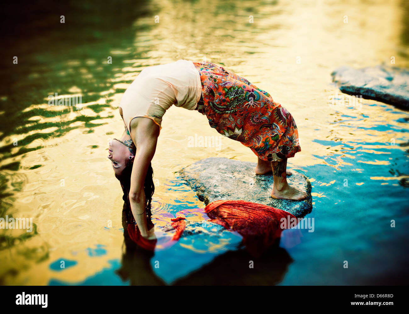 Yoga Woman outdoors in yoga pose urdhva dhanurasana in a colorful pond. - Stock Image