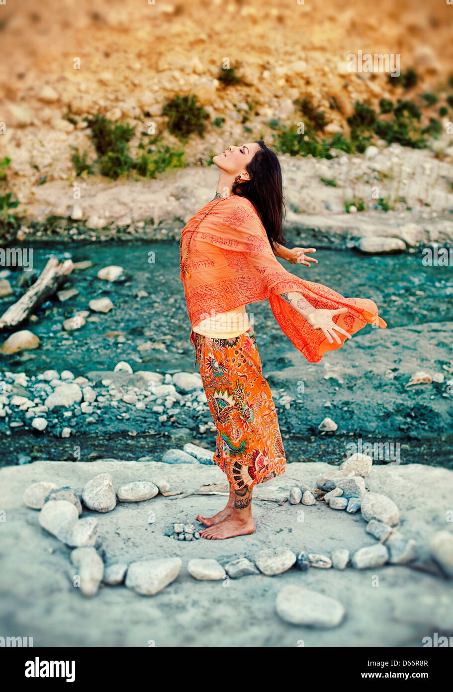 Woman outdoors near a river with her arms and heart open in a mandala of stones. - Stock Image