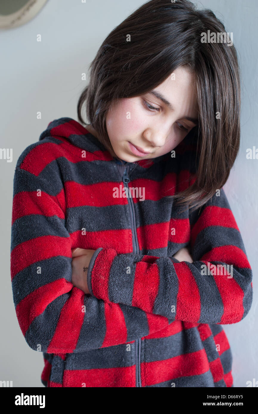Sulky or sad little white girl with dark hair looking down with her arms folded wearing a grey and red striped zip - Stock Image