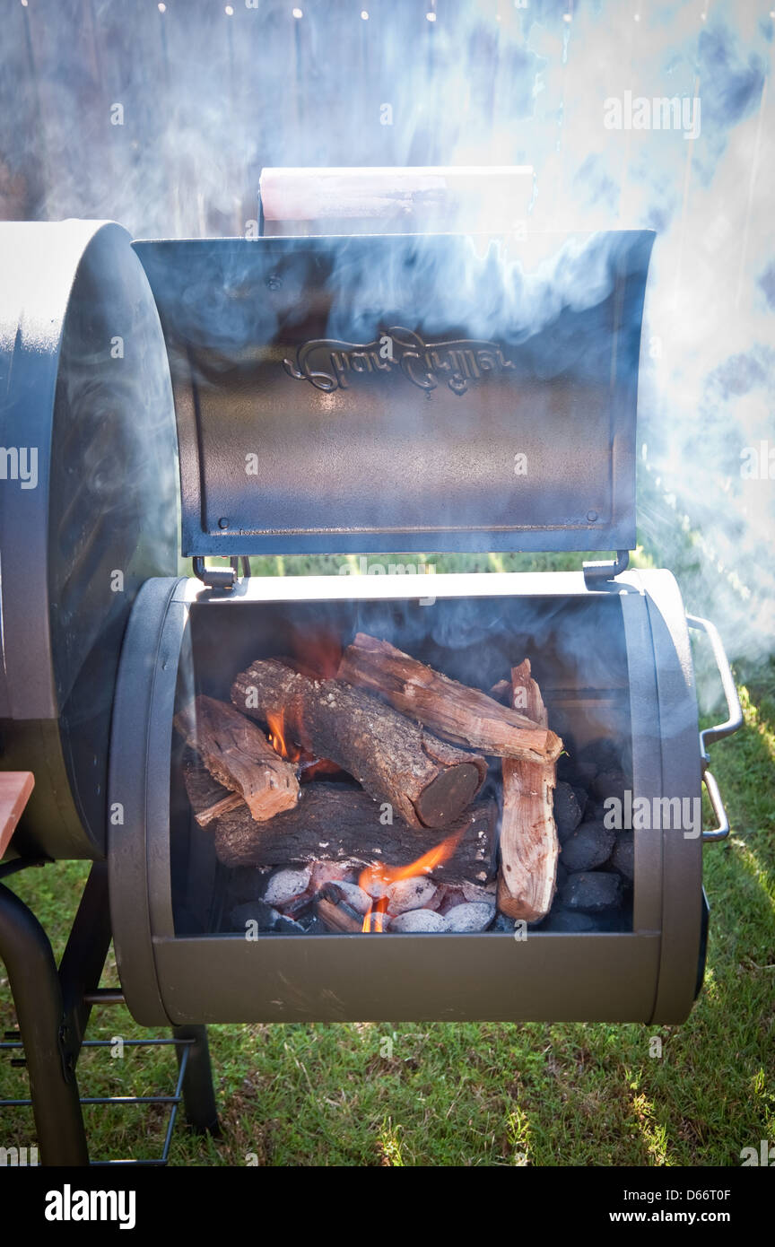Backyard smoker making Texas barbeque with Mesquite - Stock Image