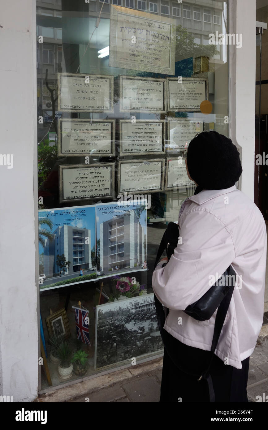 An Israeli woman reading sale and rental housing offers in a Real Estate broker office in Tel Aviv Israel Stock Photo