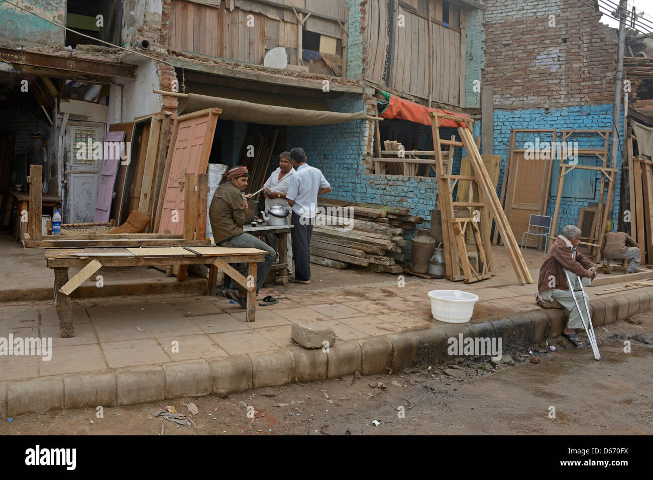 Residents living and working in these unfinished buildings in a slum area of Delhi in India - Stock Image
