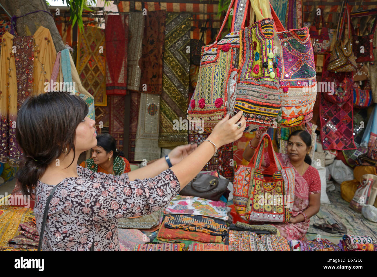 A young girl admiring a hand-made should bag at a side street market in New Delhi, India - Stock Image