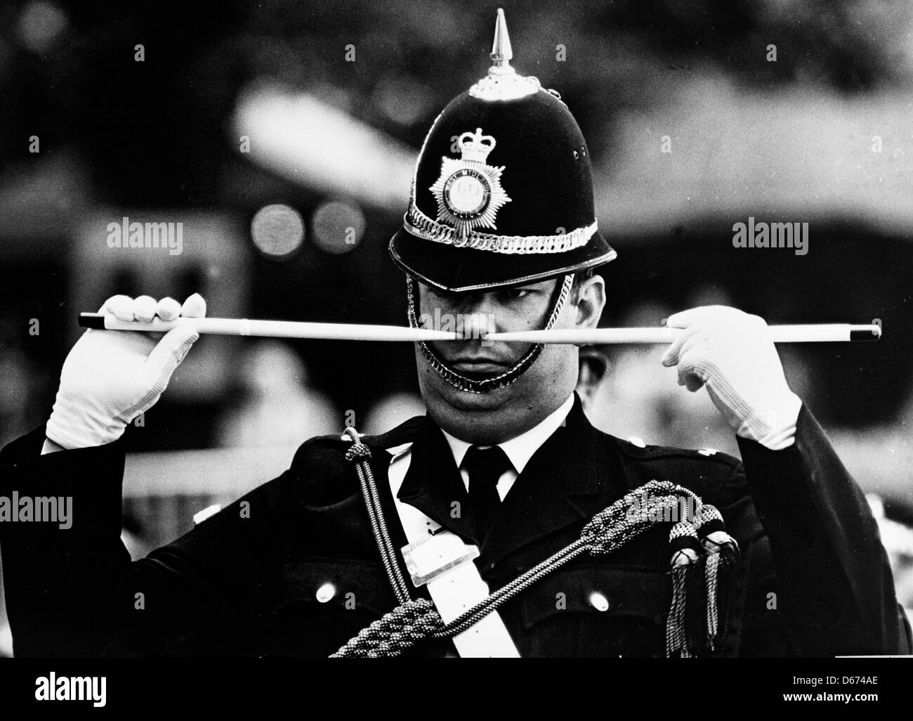 A police band member holds drumsticks to his nose during a public display in the UK - Stock Image