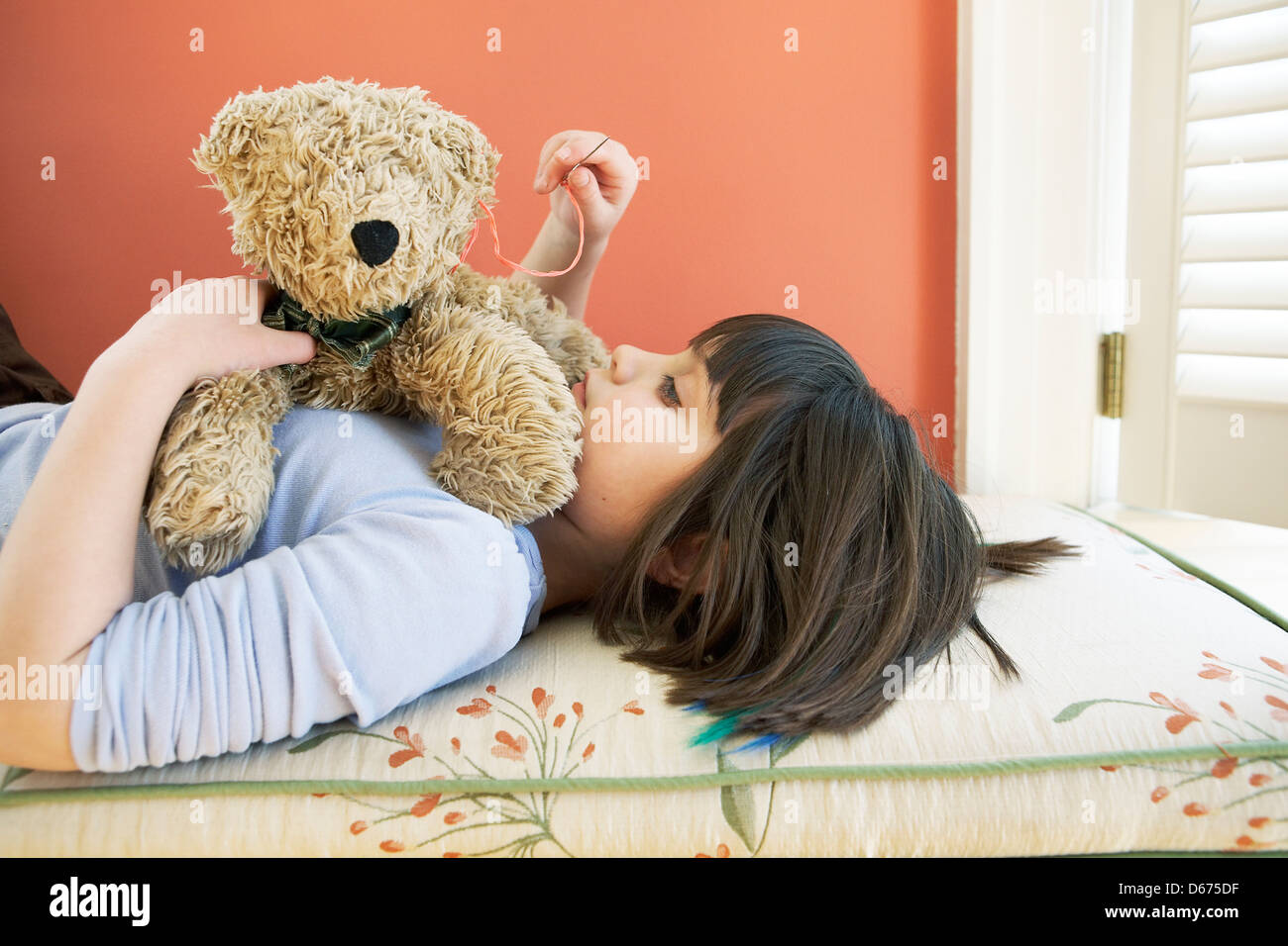 7 year old mending teddy bear - Stock Image
