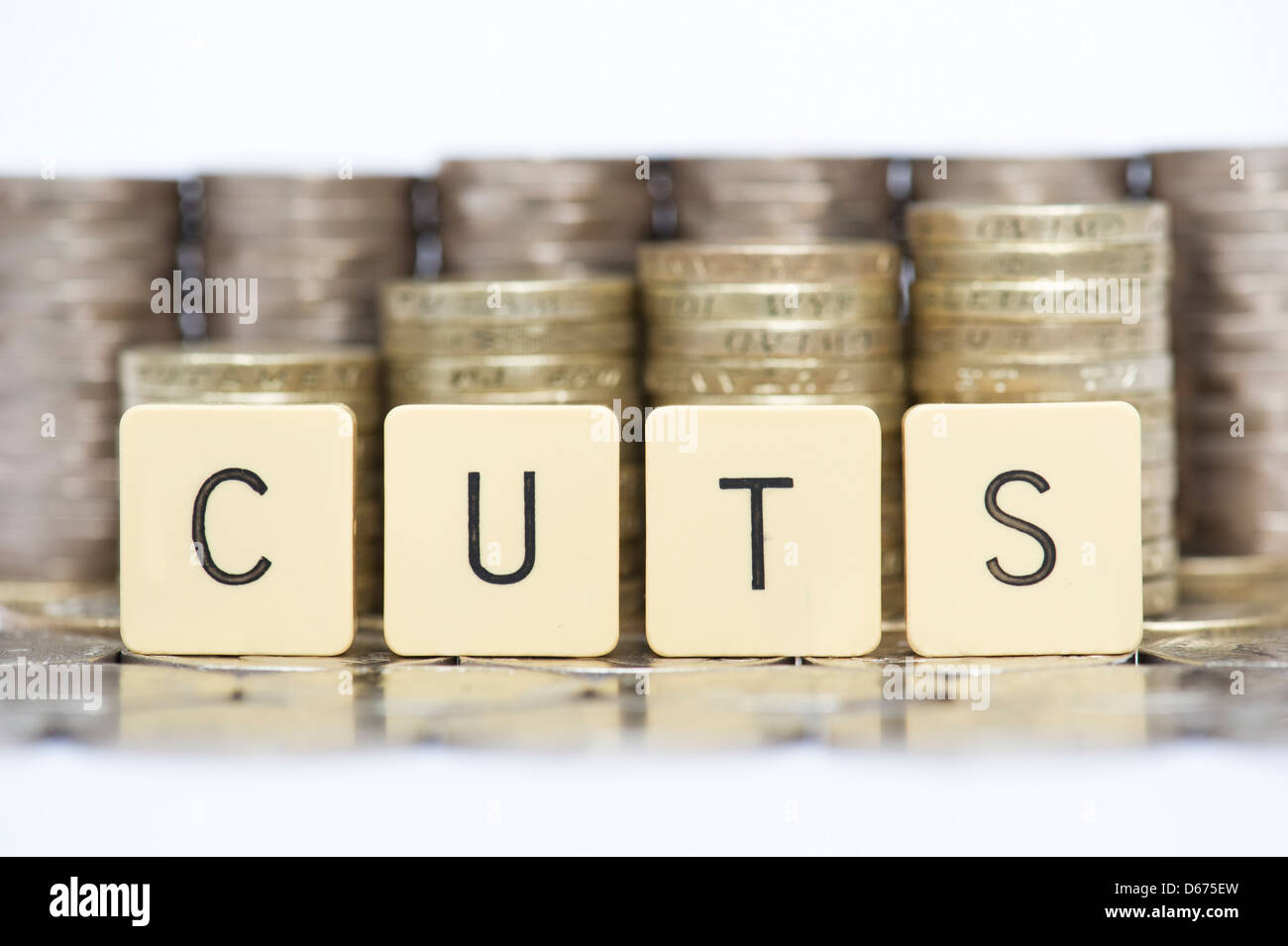 The word CUTS in front of stacks of English twenty pence and one pound coins - Stock Image