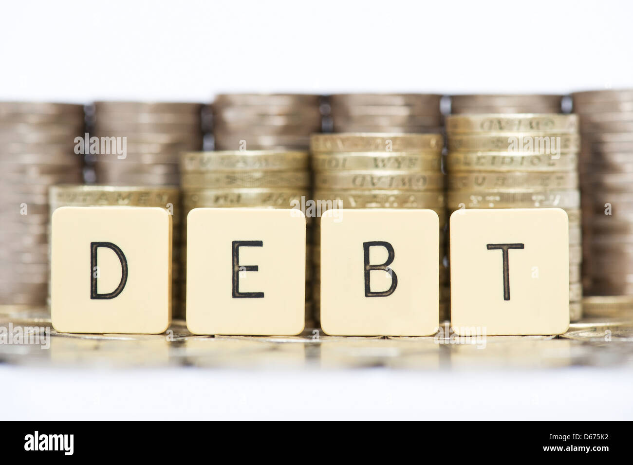 The word DEBT in front of stacks of English twenty pence and one pound coins - Stock Image