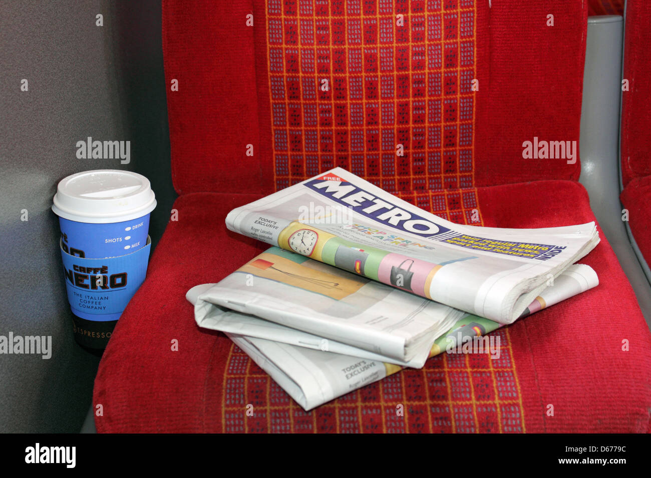 Seat on a South West Trains commuter train with empty coffee cup and the Metro free newspaper. Surrey England UK - Stock Image