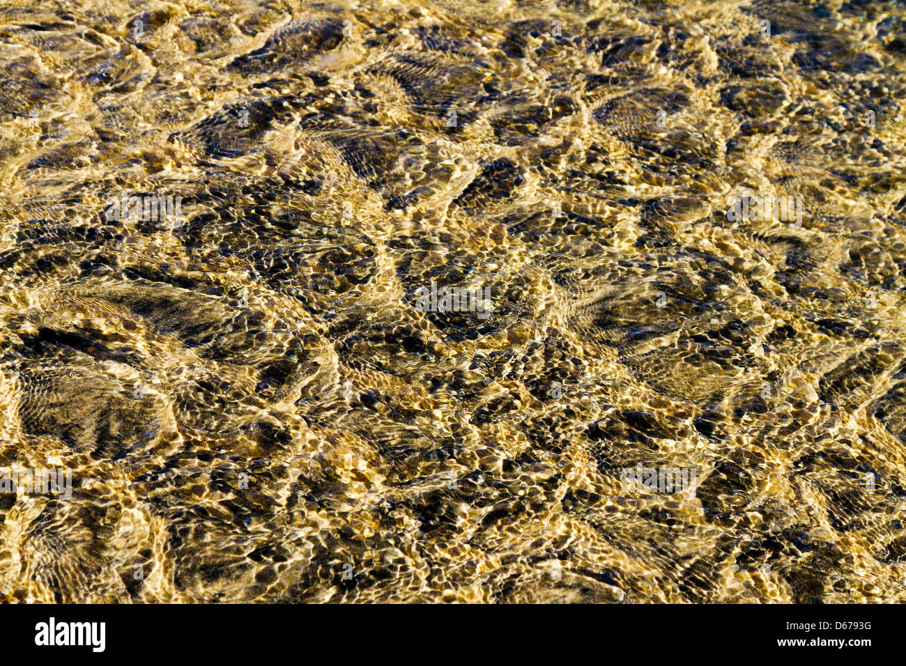 Water rippling over sand in a shallow creek bed forming artistic patterns. - Stock Image