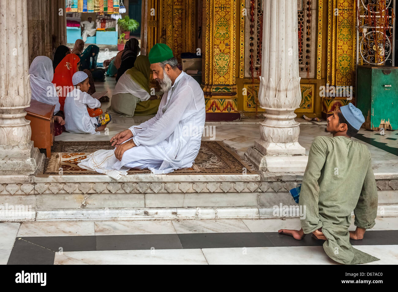 A man with green hat prays whilst disabled beggar waits patiently for alms at mosque in Nizamuddin, Old Delhi, Delhi, - Stock Image