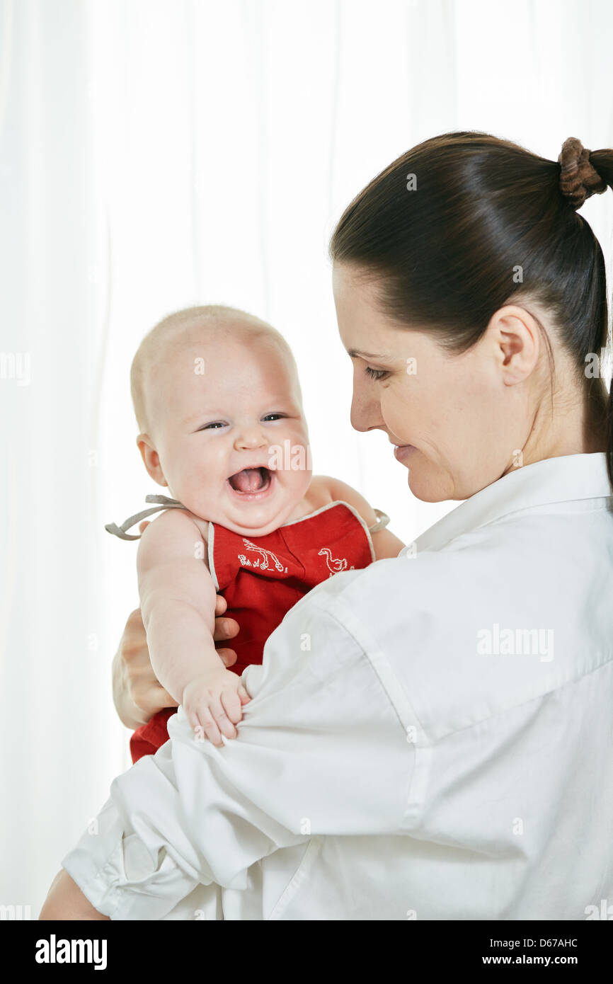 Mother with her happy child on arms on white background - Stock Image