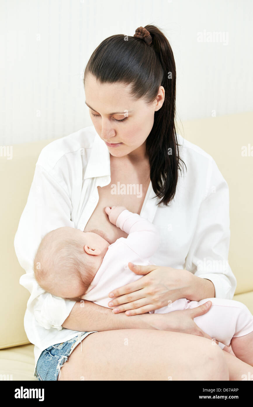 Mother nurse her child on a sofa Stock Photo