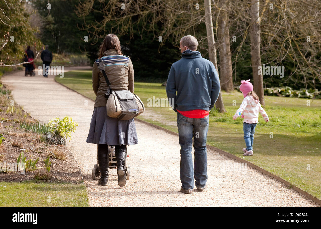 A family walking in the park, mother father and child seen from the rear, UK - Stock Image