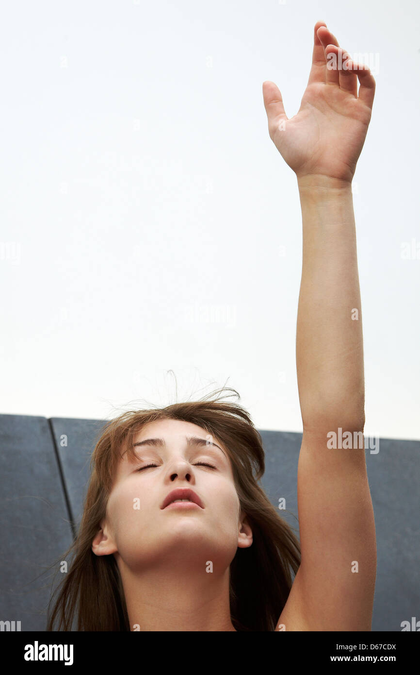 Teen girl reaching for the sky - Stock Image