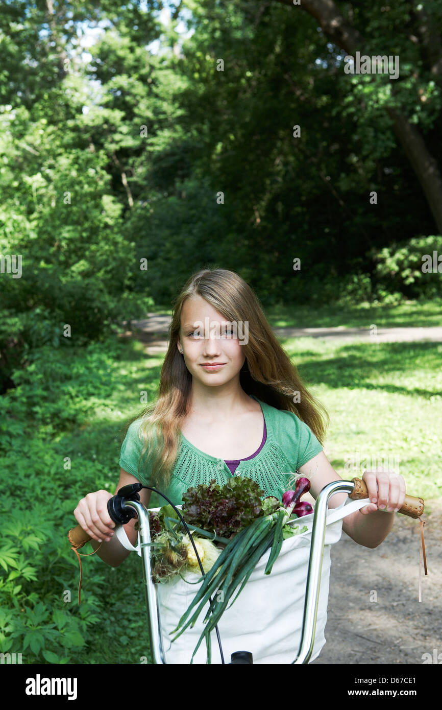 girl riding bike home from farmers market - Stock Image