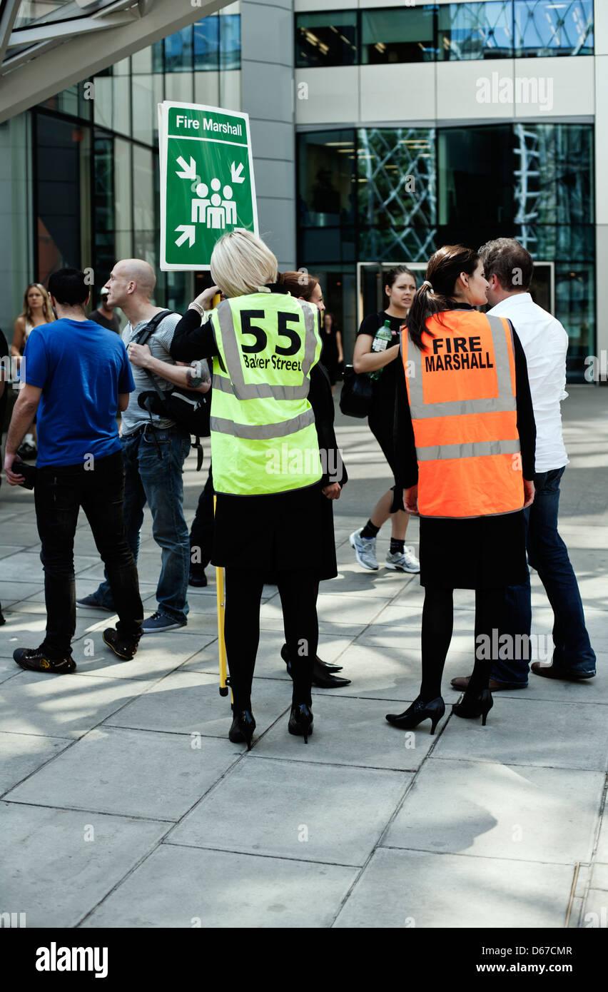 Staff assemble at fire safety point outside, 55 Baker Street, Marylebone, London, UK, Europe - Stock Image