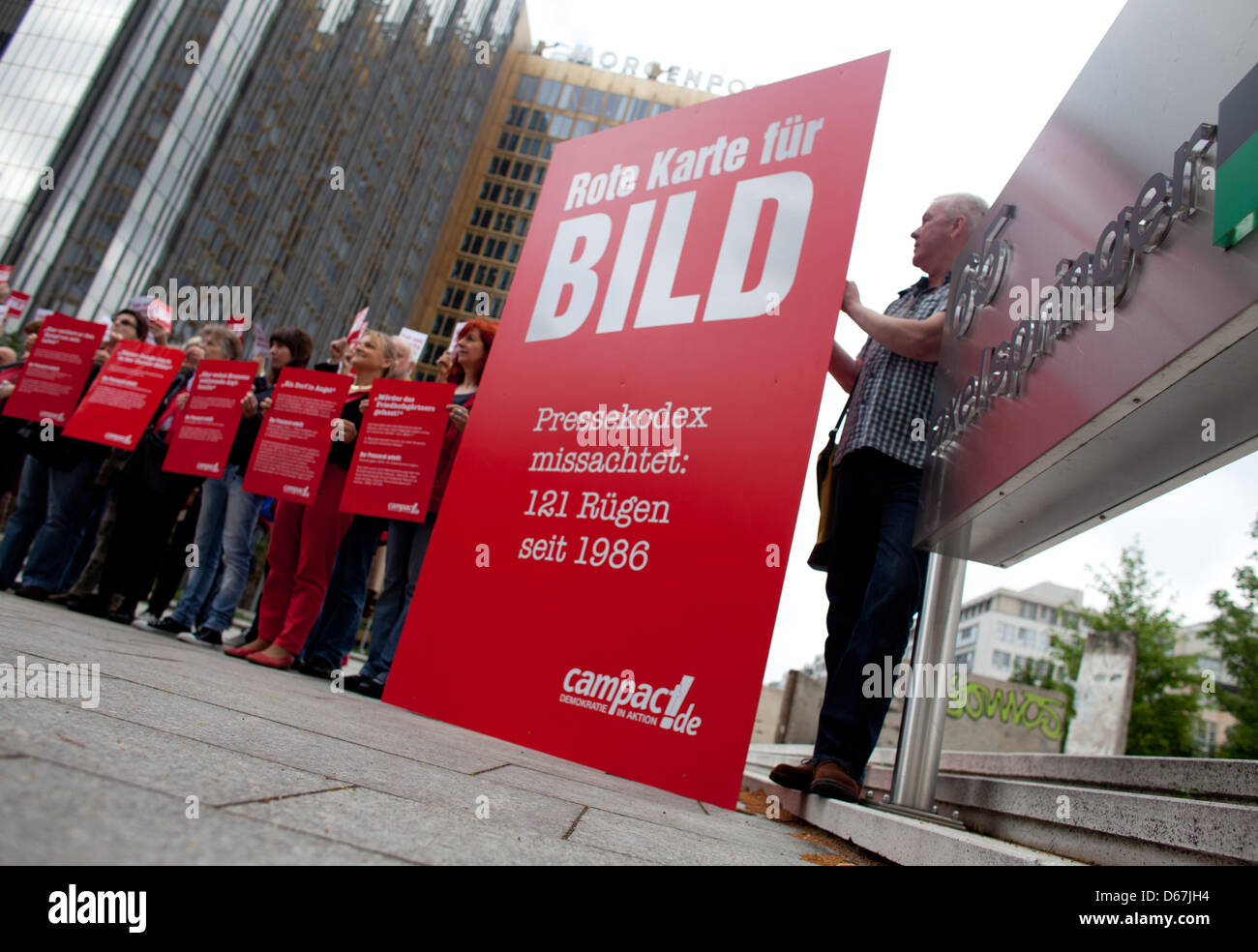 Protesters hold up red cards against BILD, a publication by Springer, at the Springer media headquarters in Berlin, Stock Photo