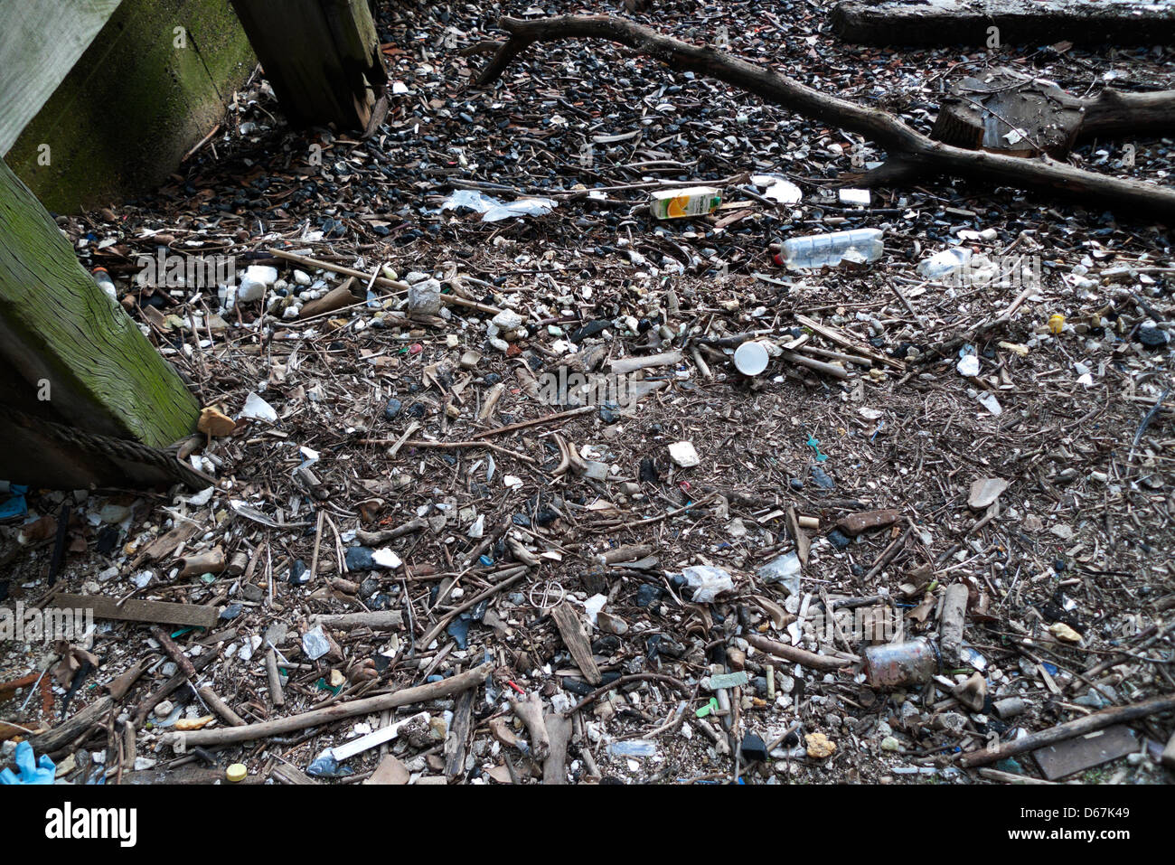 Detritus, broken pottery, glass and clay pipes on the riverbank foreshore of the River Thames at Queenhithe, City - Stock Image