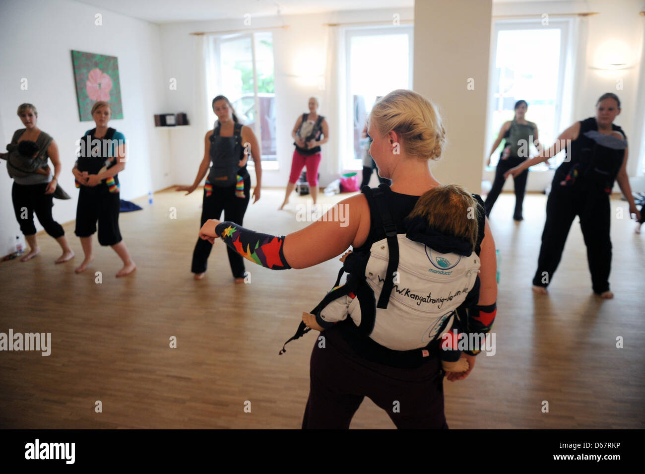 Mothers with their babies are pictured with instructor Simone Koch (front) during Kanga training in Berlin, Germany, - Stock Image