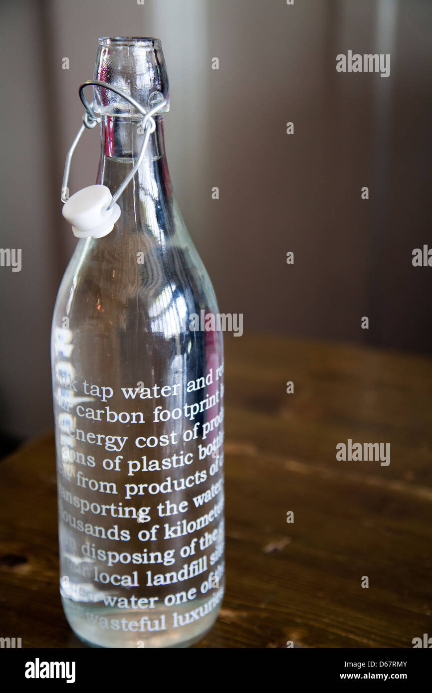 Bottle of Tap water with Carbon footprint Message in favor of Glass as opposed to Plastic - UK - Stock Image