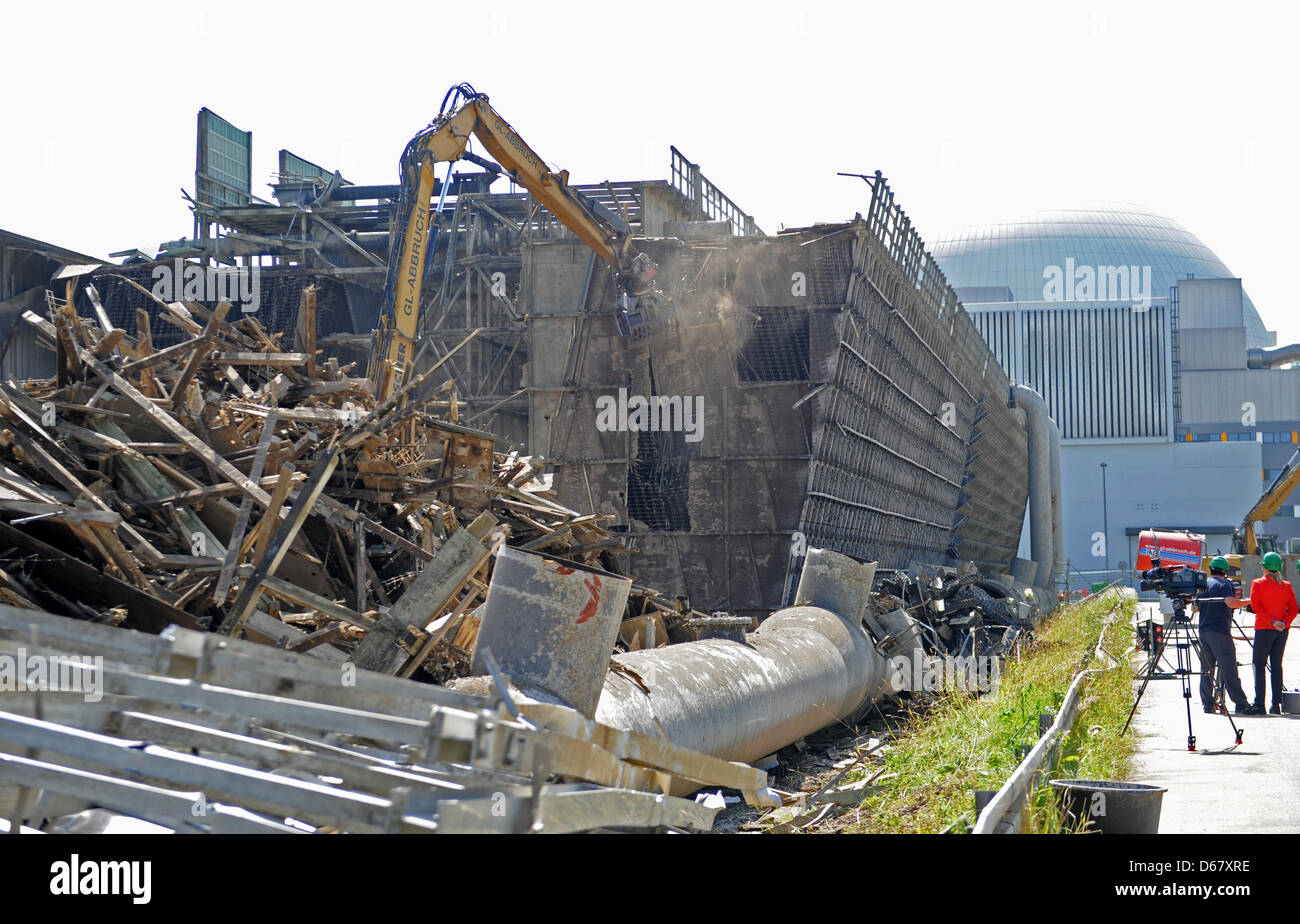 An excavator demolishes a cell cooling tower of the nuclear
