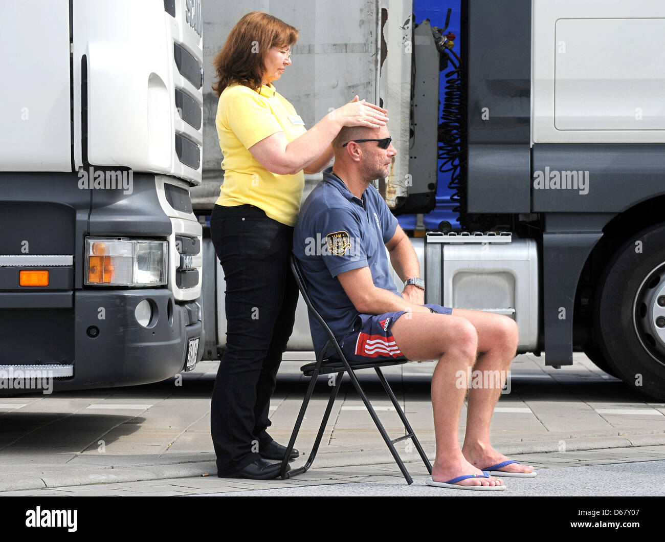 Truck driver Thomas Schallock from Oldenburg receives a Reiki treatment by Renate Holzfoerster at the rest house - Stock Image