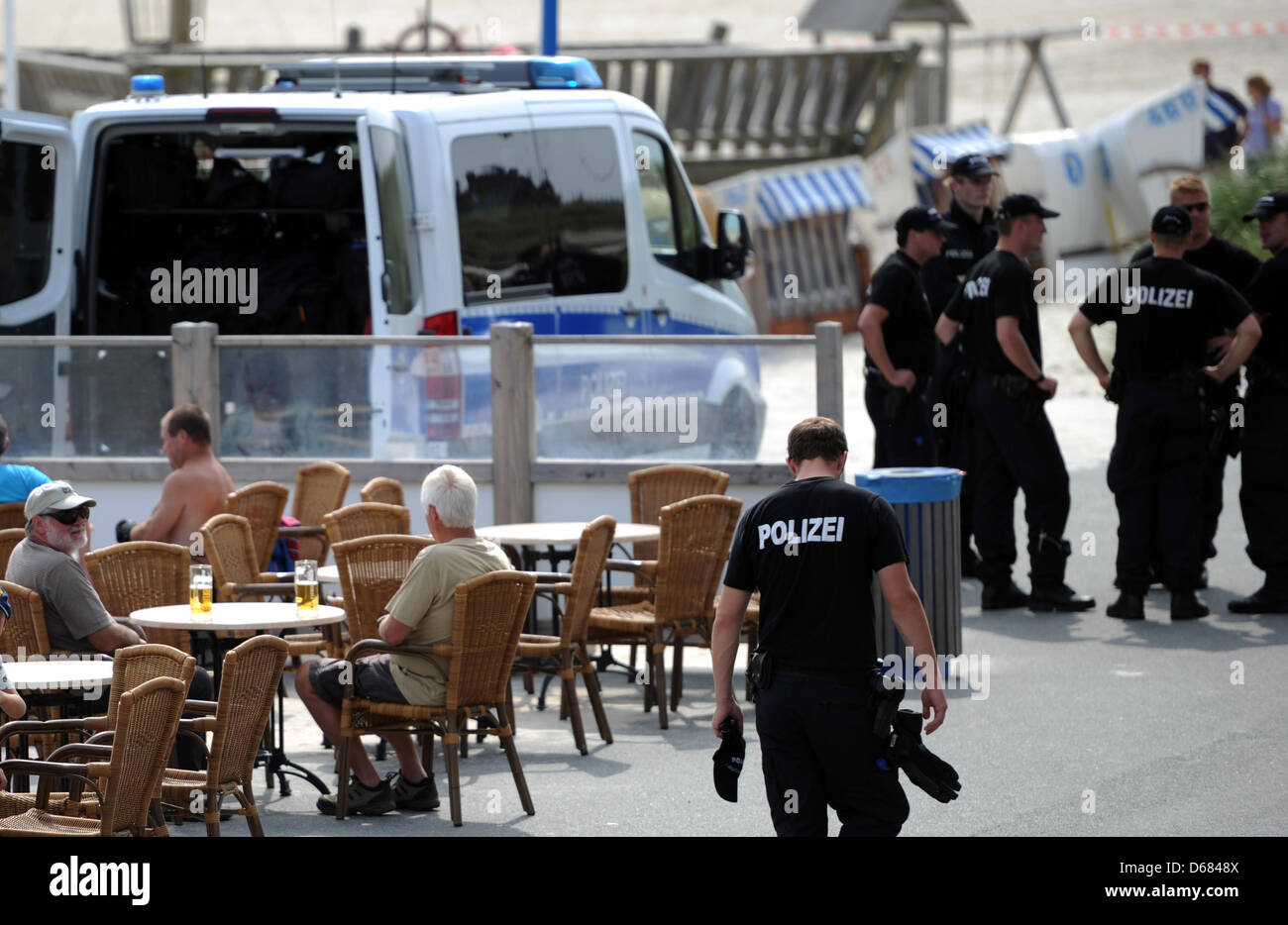 Pensioners sit and drink beer while police officers leave the site where they found the body near the playground - Stock Image