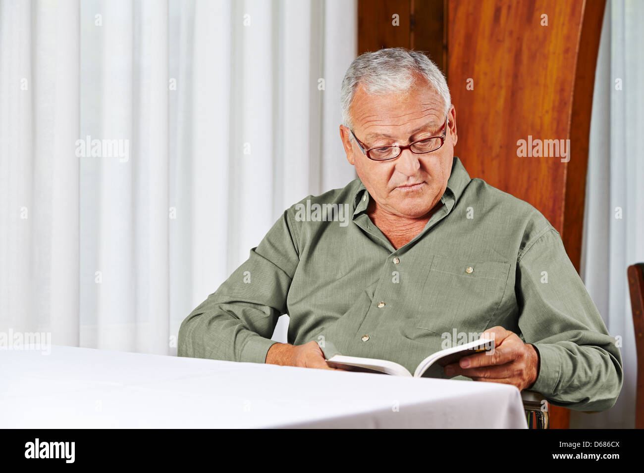 Senior man in rest home reading a book with reading glasses - Stock Image