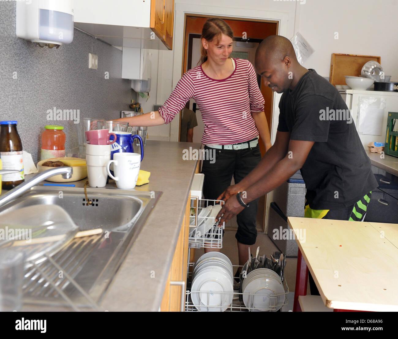 Abduorahmane Seck (R) from Senegal and after-school-care teacher Juliane Pfeffer work in the kitchen at Karl Schubert Stock Photo