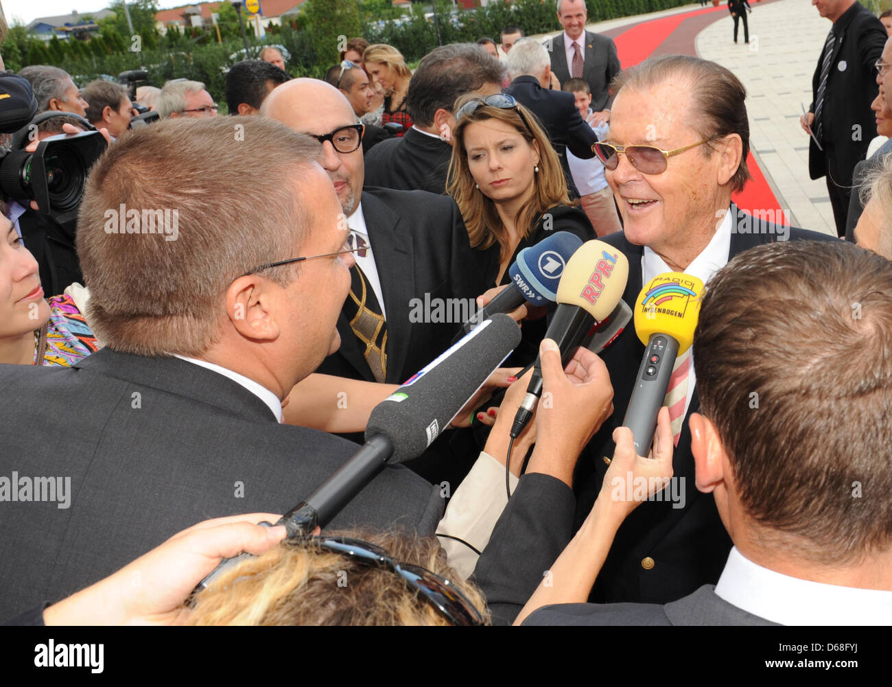 British actor Sir Roger Moore gives an interview in front of the new hotel 'Bell Rock' at theme park Europa - Stock Image