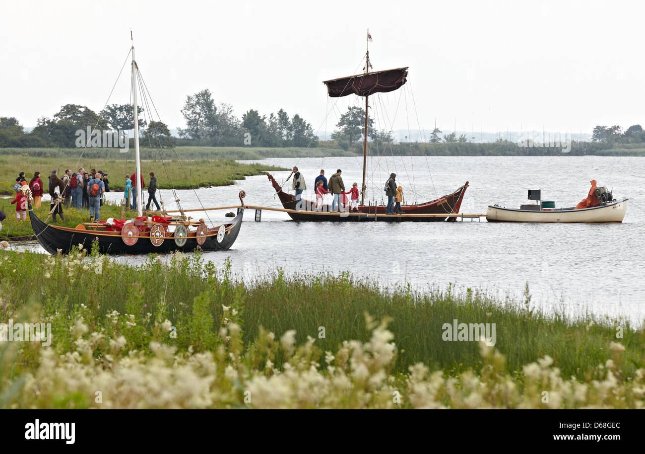 Visitors observe Viking ships during the event 'Kurs Haithabu' in Busdorf, Germany, 14 July 2012. 'Kurs - Stock Image