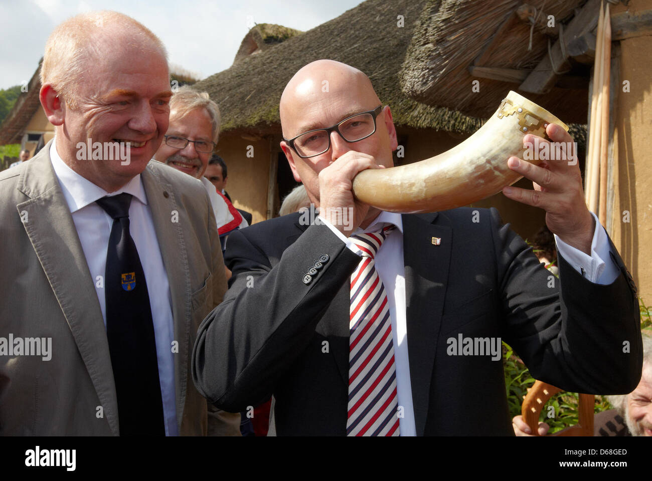 Premiere Thorsten Albig (R) blows a horn next to mayor Ralf Feddersen during the event 'Kurs Haithabu' in - Stock Image