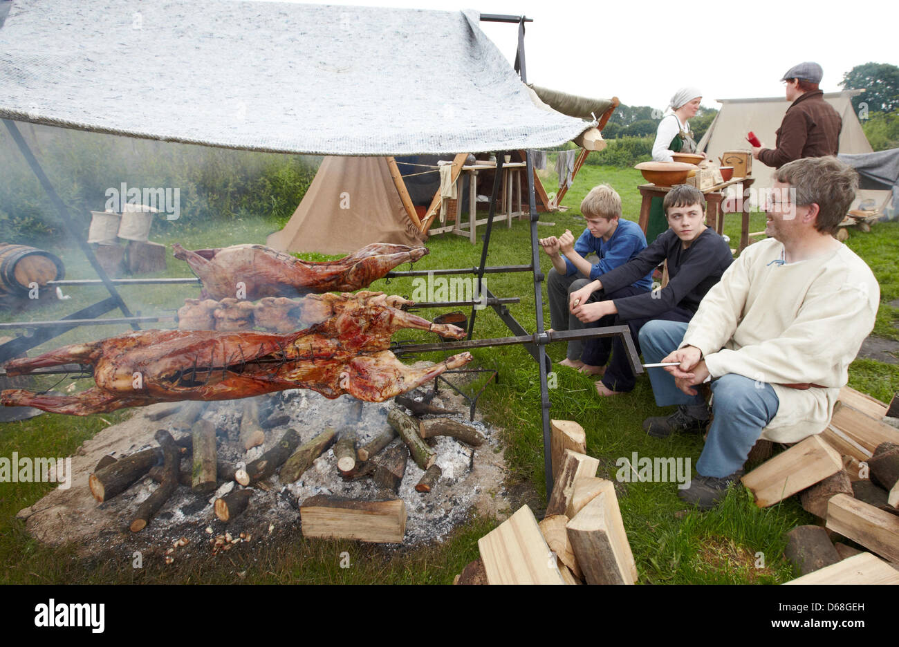 Johann Nueborg from Denmark (R) and his sons, Klaus and Nikolej have a barbeque during the event 'Kurs Haithabu' - Stock Image