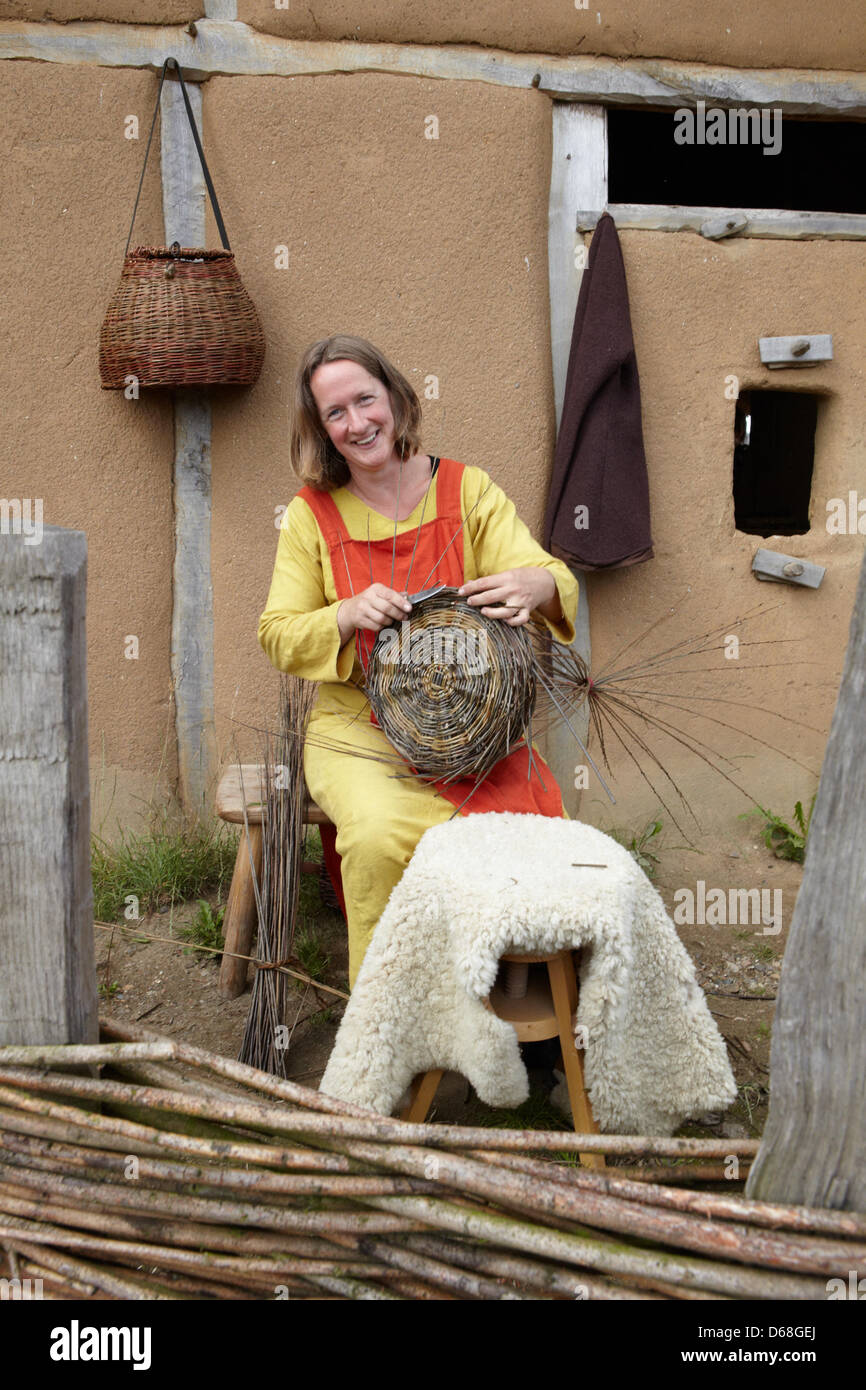 Kirsten Rudolf shows visitors how to weave a basket  during the event 'Kurs Haithabu' in Busdorf, Germany, - Stock Image