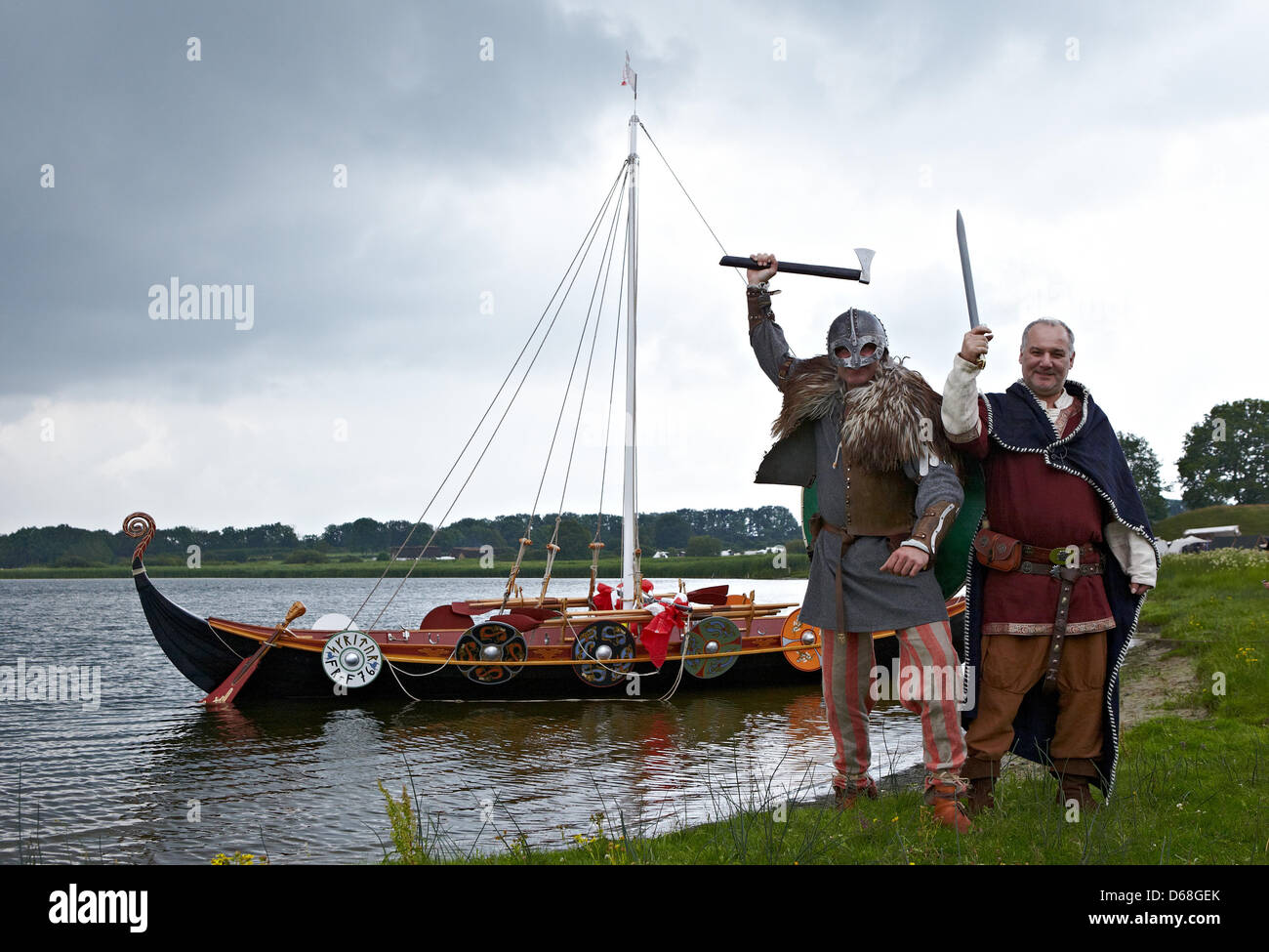 Henning Messner (L) and Martin Mueller pose for the camera net to  the Viking ship Selker Noor during the event - Stock Image