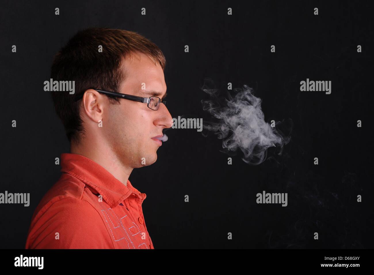 Man blowing smoke - Stock Image
