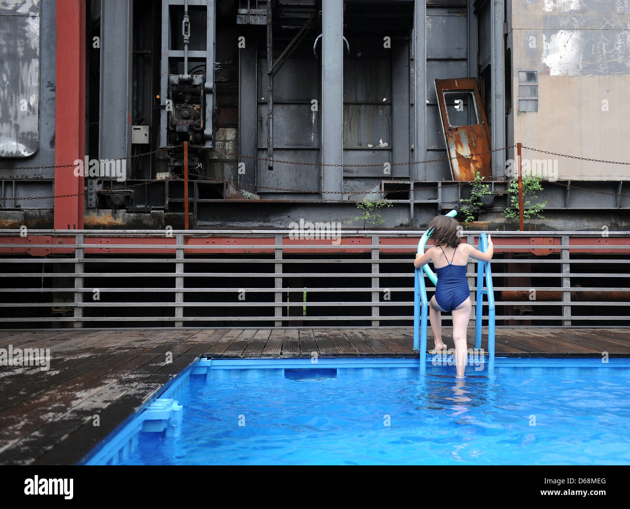 A girl climbs out of the pool at the Zollverein Coal Mine Industrial Complex in Essen, Germany, 18 July 2012. The - Stock Image