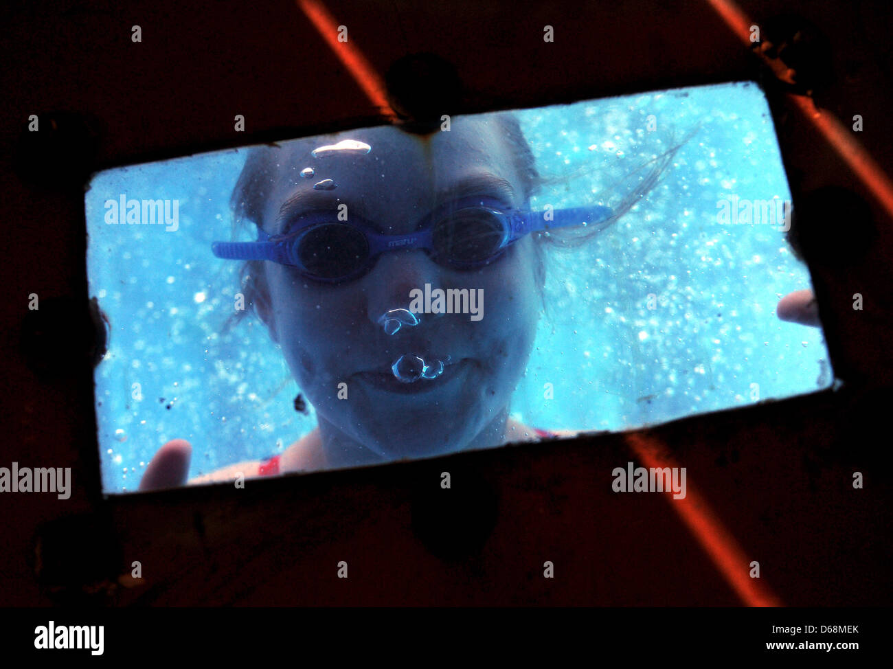 A girl with diving goggles looks through a window in the pool at the Zollverein Coal Mine Industrial Complex in - Stock Image