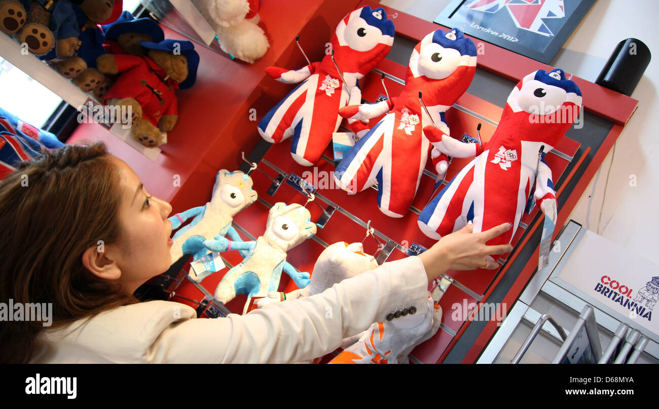 Ryoko Sato reaches for the official olympic mascot 'Wenlock' in a souvenir shop in London, Great Britain, - Stock Image